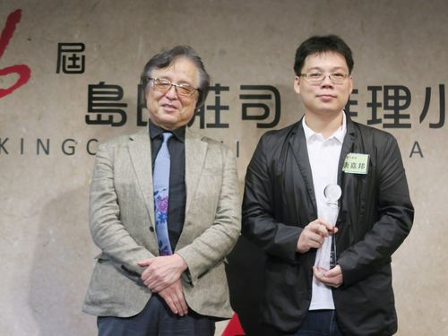 島田荘司さん(左)からトロフィーを贈られた唐嘉邦さん