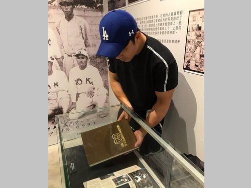 展示ケースに「能高団」関連の資料を入れる周思齊選手=台中市野球教育基金会提供