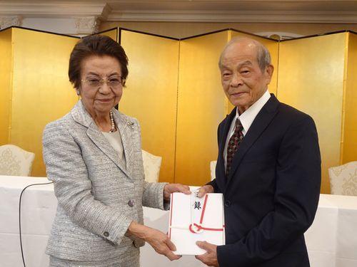 「桜里帰りの会」の台湾側会長、黄石城氏(右)から目録を受け取る安倍洋子氏