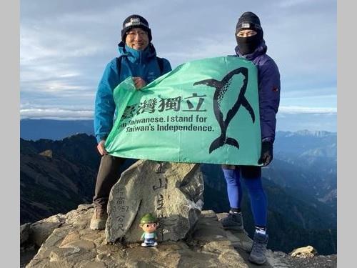 玉山の頂上で「台湾独立」旗を掲げる陳致中氏(左)=同氏のフェイスブックから