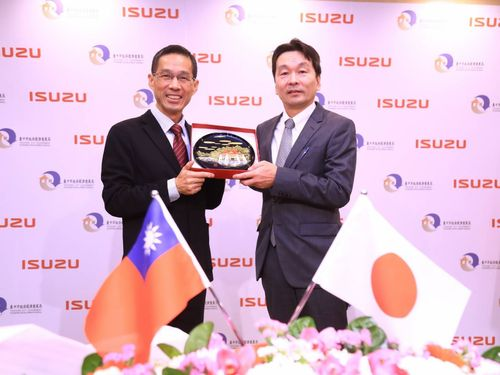 台中市経済発展局の張局長(左)から記念品を贈られるいすゞの合田海外営業第三部長=同市政府提供