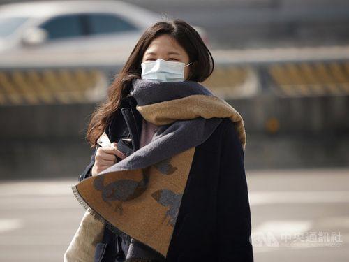 コートやストールをはおって外出する女性=30日朝撮影