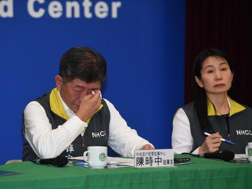 記者会見で涙を拭う陳衛生福利部長(左)