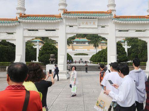 故宮博物院の前広場で記念写真を撮る観光客たち