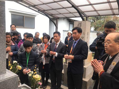 龍肚小学校2代目校長・六山春英さんの墓前で線香を手向ける同小の児童ら=同小提供