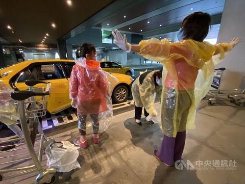 せきがあるため、空港から集中検疫所に直接収容されることになる女児とその母親=4月3日、桃園空港