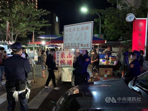 ナイトマーケットで行楽客たちに屋外1メートル、室内1.5メートルの社会的距離を保とうとプラカードを掲げ呼びかける警察官ら