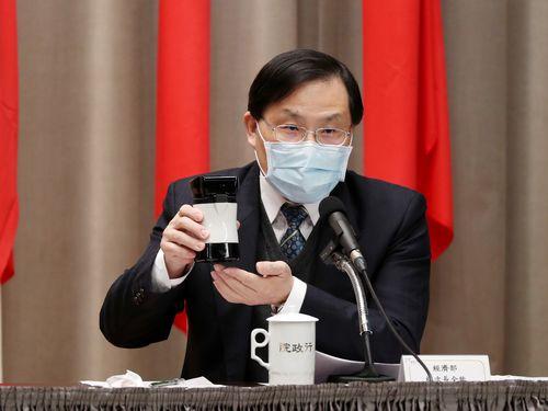 新型コロナウイルスを検出するPCR検査機器の原型品を手に持つ経済部の林次長