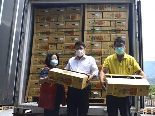 屏東県産パイナップルの日本向け輸出を喜ぶ潘県長(中央)=同県政府提供