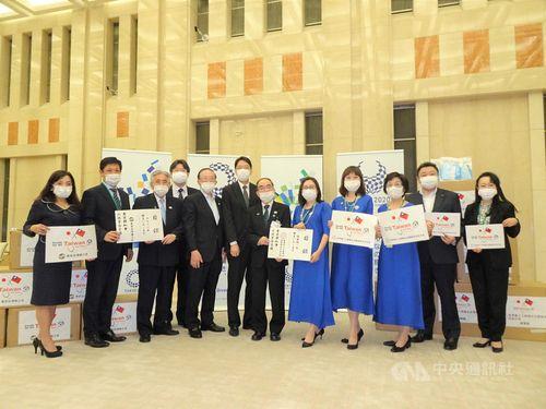 世界華人工商婦女企管協会日本分会の銭会長(右5)から目録を受け取る東京都の多羅尾副知事