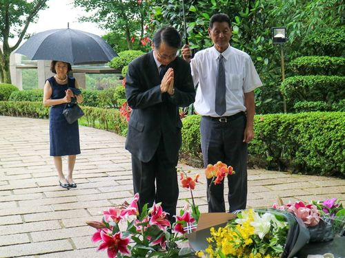テレサ・テンさんの墓前に手を合わせる日本台湾交流協会台北事務所の泉裕泰代表=同協会のフェイスブックから