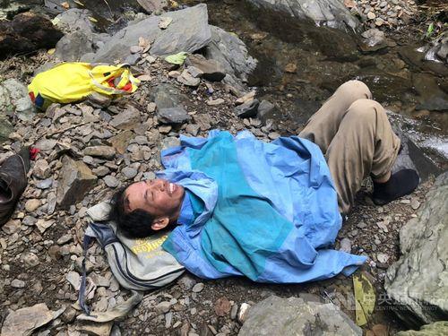 登山道から約20メートル下の谷間に発見された楊さん=消防提供