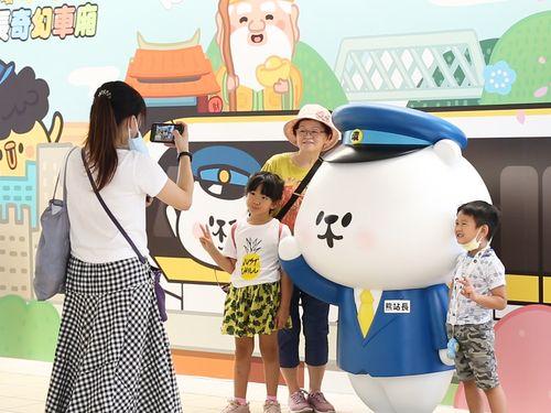 台北メトロ環状線の新キャラ、「熊駅長」と記念撮影する利用者たち=新北市政府捷運工程局提供
