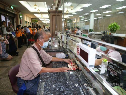 郵便局で紙製の「振興三倍券」を購入する男性