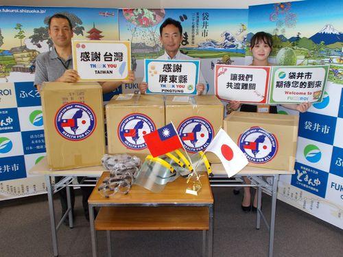 屏東県からの医療物資を前にプラカードで感謝を伝える袋井市の人たち=同県政府提供