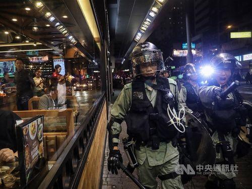 デモ隊を追い払う香港の警官とその様子を見つめる香港市民