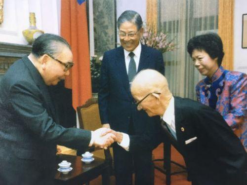 蒋経国総統(左手前)と握手を交わす李金龍氏。奥は笑顔の李登輝副総統夫妻。肩書はいずれも1985年当時のもの=総統府提供