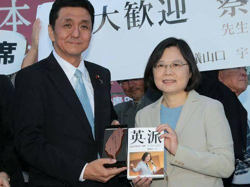 岸氏(左)に自著の「英派」を贈る蔡氏=2015年10月7日に山口県で撮影、民進党提供