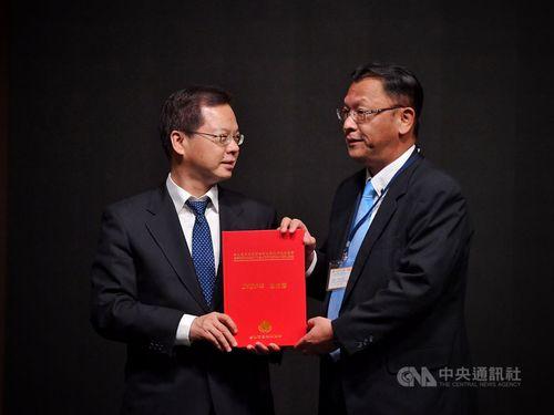 台北市日本工商会の大恵理事長(右)から白書を手渡される国家発展委員会の龔主任委員