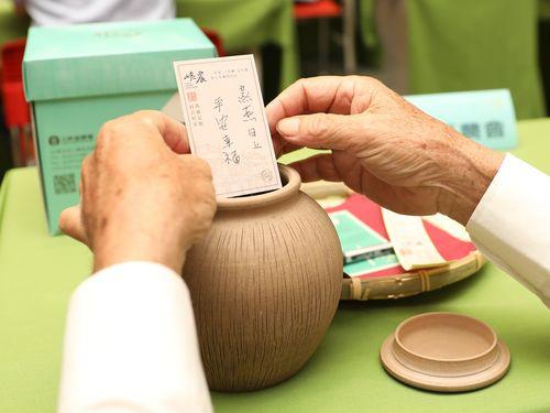 茶葉が入った陶器の茶つぼに願い事を書いた紙を入れて封をする「封茶」の行事=同農会のフェイスブックページより