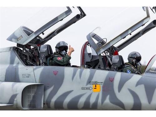 後部座席でポーズを決める空軍の熊司令官(左)=国防部提供