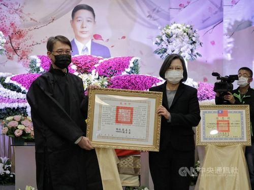 熊震球さんの長男の鼎さん(左)に「褒揚令」を手渡す蔡総統=総統府提供