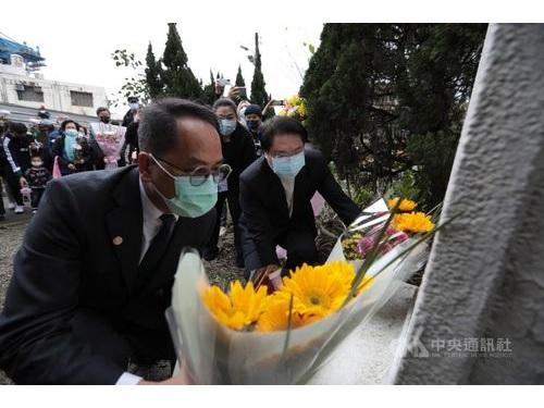 記念碑に花を添える林基隆市長(右)と彭文化部次長(左)=同市政府提供