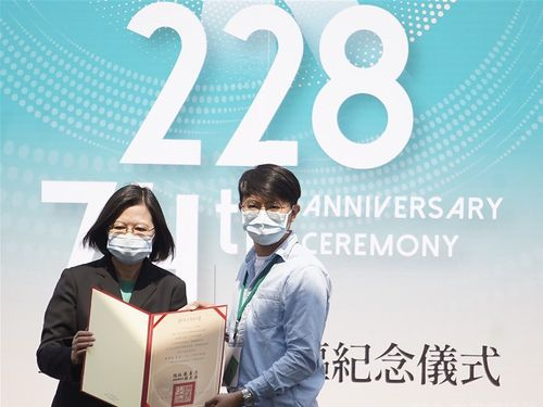 2・28事件の被害者遺族に「名誉回復証書」を贈る蔡総統(左)