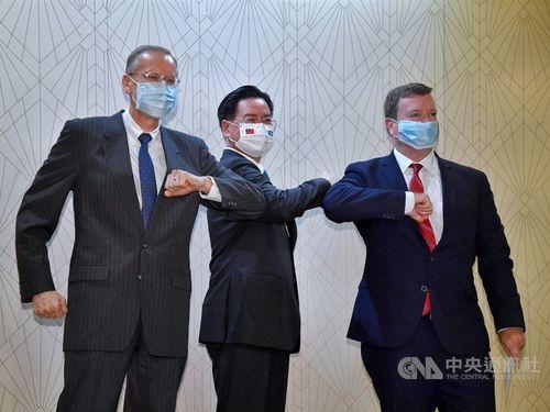 肘タッチを交わす(左から)AITのクリステンセン台北事務所所長、呉外相、ヘネシー-ナイランド駐パラオ米国大使