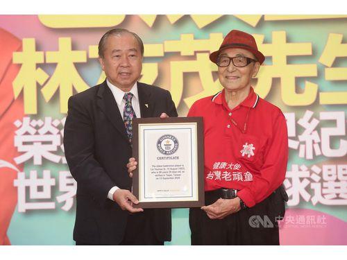 世界華人バドミントン聯合会(全球華人羽毛球聯合会)の呉俊彦会長(左)から認定証を贈られる林友茂さん(右)
