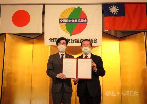 永井大阪市議(左)から「全国日台友好議員協議会」の決議文を手渡される謝駐日代表