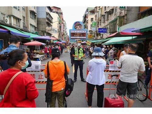 台北市の伝統市場の入り口でマスク着用など感染対策を呼び掛ける警察官