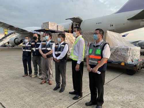 陰圧ブースを積んだ貨物機を出迎える陳衛生福利部長(右から3人目)