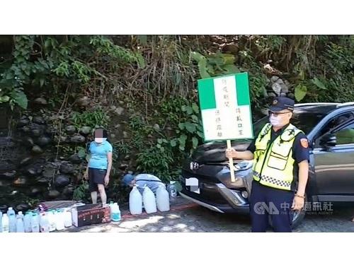 午時水を汲みに来た市民(左)と感染対策を呼び掛ける警察(写真=読者提供)
