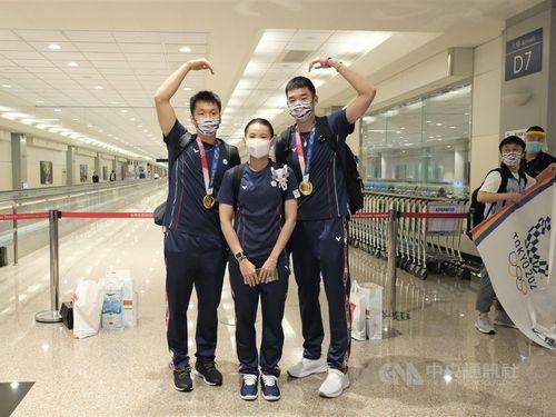 4日夕、桃園国際空港に到着した東京五輪バドミントン男子ダブルス金メダリストの李洋(左)、王斉麟(右)、同女子シングルス銀メダリストの戴資穎(中央)