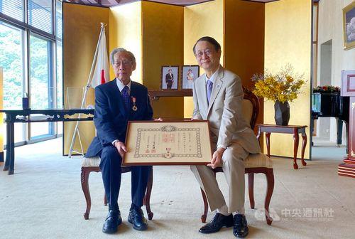 日本台湾交流協会台北事務所の泉裕泰代表(右)から勲章を贈られた蔡焜霖さん