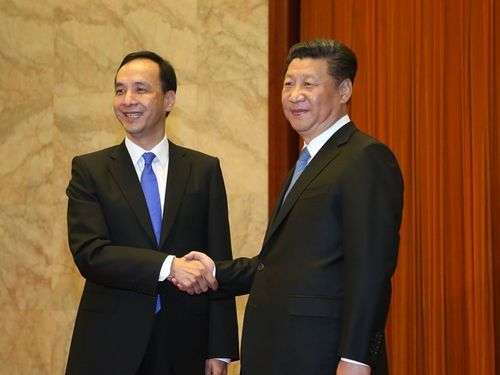 習近平氏(右)と握手する朱立倫氏=2015年、北京