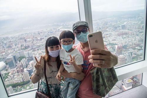 台北101の展望台で自撮りする親子=資料写真