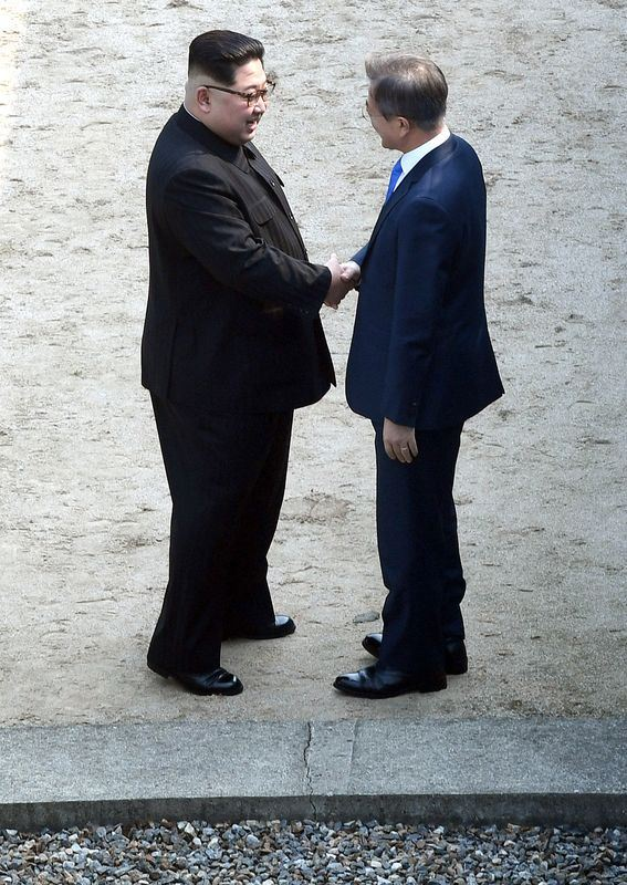 兩韓峰會27日登場,北韓領導人金正恩(左)跨越北緯38度的軍事分界線,在金正恩邀請下,文在寅(右)也跨過北緯38度分界線,短暫踏上北韓領土。(韓聯社提供)