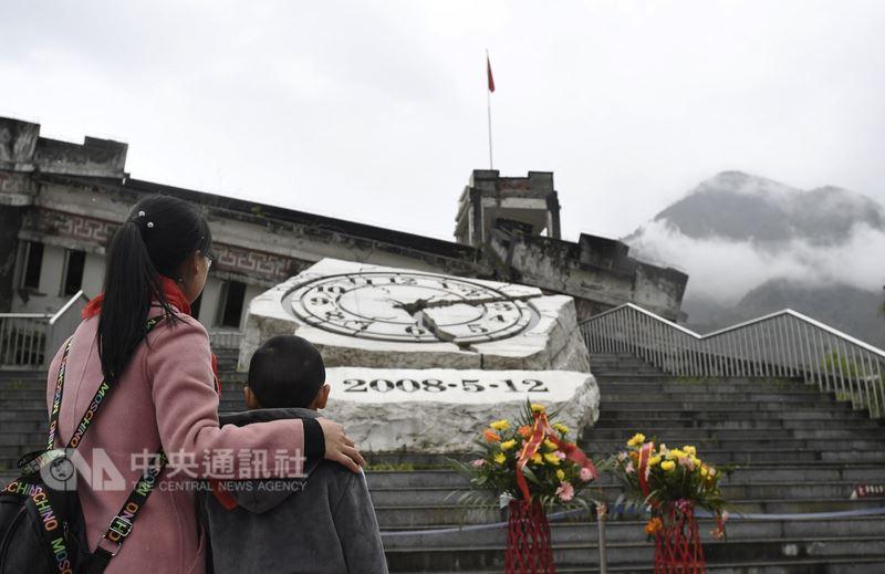 2018年清明節,民眾在四川省汶川縣映秀鎮的地震遺址前。時鐘雕塑的指針裂痕,記錄著2008年5月12日下午2時28分大地震發生的時刻。(中新社提供)中央社 107年5月12日