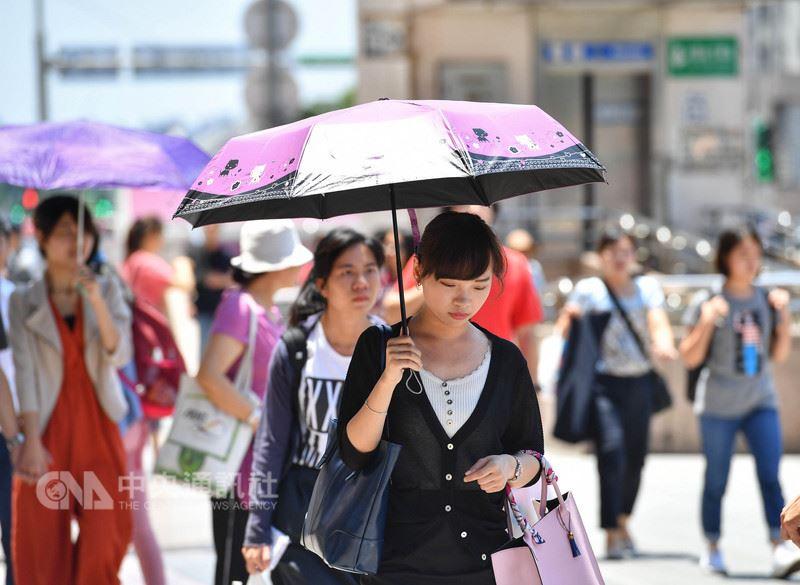 中央氣象局觀測,台北市27日氣溫飆到攝氏38.2度,是今年全台新高溫。圖為台北市街頭民眾用傘遮陽。中央社記者王飛華攝 107年5月27日