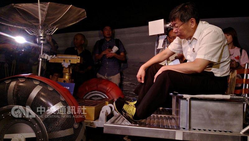 台北市長柯文哲(前)5日出席台北市立天文科學教育館展示場更新啟用開幕典禮,並登上模擬「阿波羅17號」登月時的擬真月面車,低頭研究月面車結構。中央社記者陳妍君攝 107年7月5日
