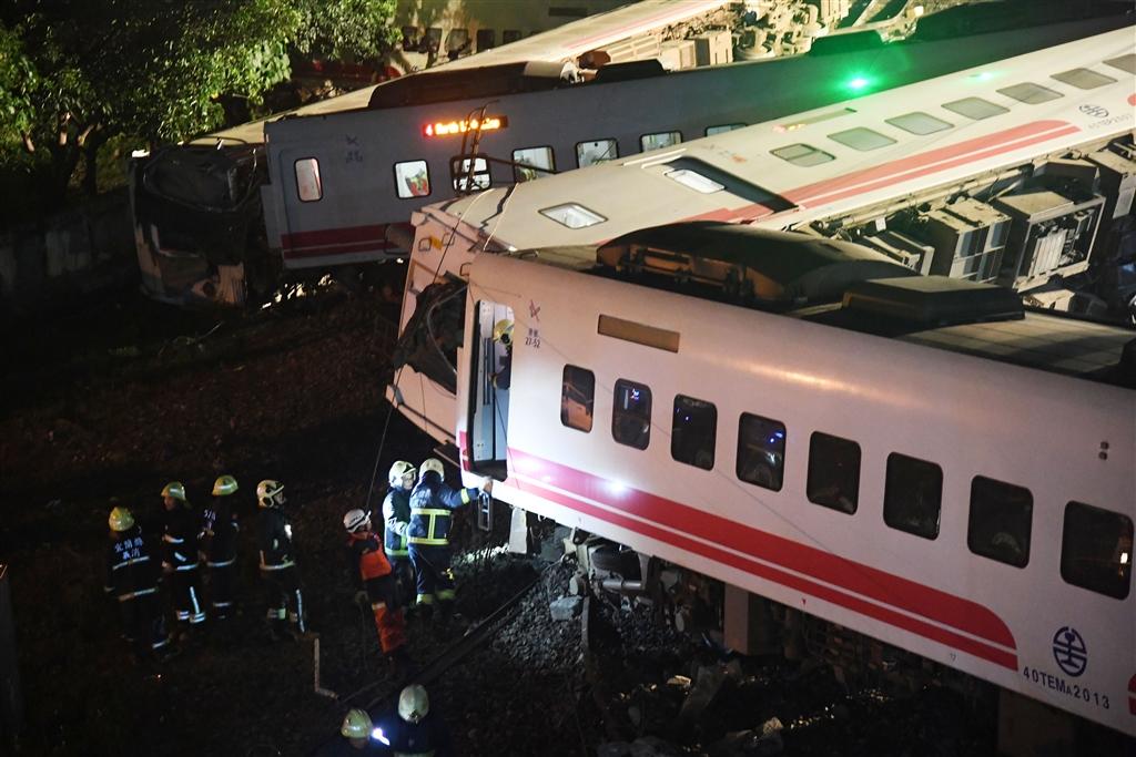 台鐵6432次普悠瑪列車21日下午在宜蘭新馬車站發生出軌翻覆事故,造成重大傷亡,各節車廂因擠壓而曲折變形,警消到場救援,在各車廂間仔細搜索,不放過任何角落。 中央社記者孫仲達攝 107年10月21日
