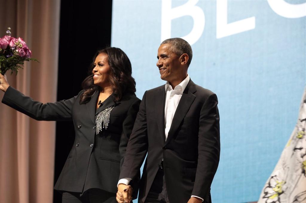 美國前總統歐巴馬(右)17日帶著粉紅玫瑰花束,意外現身愛妻蜜雪兒.歐巴馬(左)在華府第一資本球場的打書會。(圖取自推特twitter.com/MichelleObama)