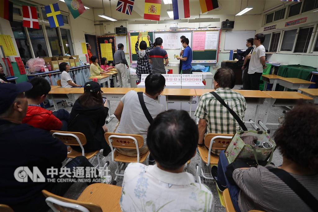 107年地方公職人員選舉及全國性公民投票案第7案至第16案24日登場,台北市士林區天玉里晚間開始進行開票作業,民眾到投開票所現場監票。中央社記者裴禛攝 107年11月24日