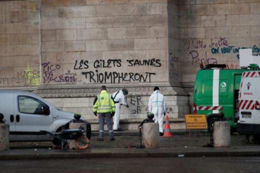 法國首都巴黎市中心爆發1968年5月學運以來最嚴重暴亂,2日可見工人清理擦洗凱旋門上的塗鴉。(路透社提供)