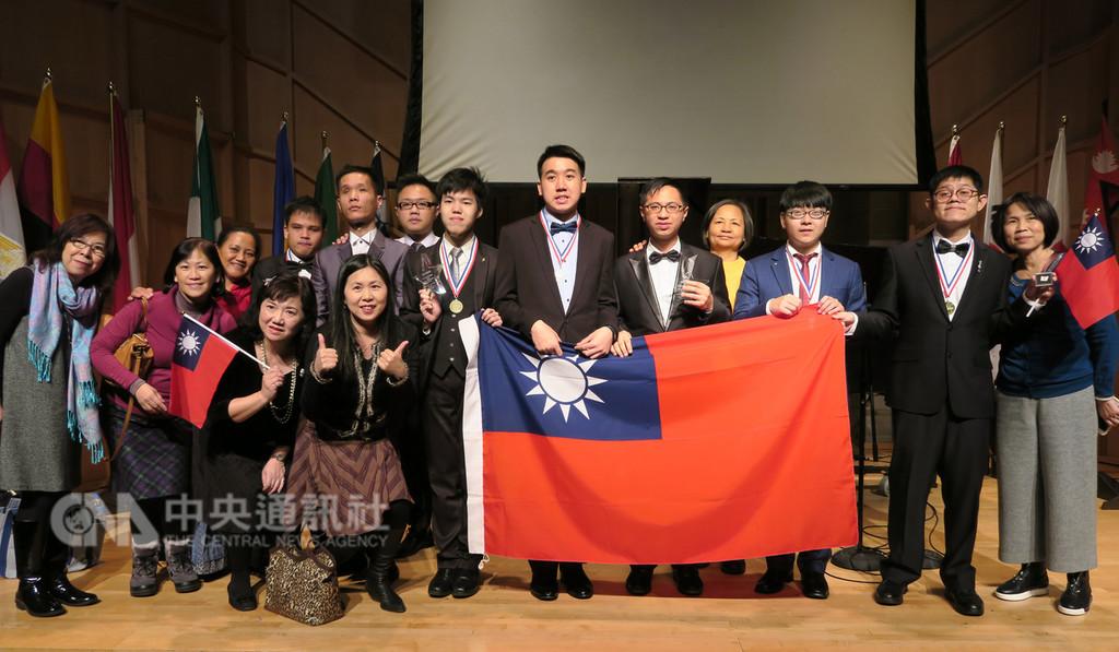 第4屆國際身障鋼琴大賽在紐約舉行總決賽,代表台灣的李尚軒(右5)奪金,王榮堅(右7)獲得銀牌。頒獎典禮後,台灣代表團上台,拉起中華民國國旗合影。中央社記者尹俊傑紐約攝 107年12月4日