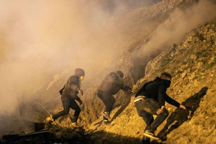 美國邊防人員1日早上扔擲催淚瓦斯到墨西哥境內,阻止一群移民跨越蒂華納的美墨邊境。(法新社提供)