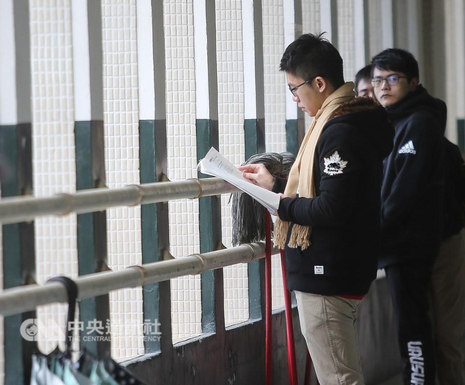 大學學測26日舉行第2天考試,遇上強烈冷氣團來襲,上午考生穿著保暖衣物、戴上圍巾,在教室外拿著教科書及參考書做最後複習。中央社記者謝佳璋攝 108年1月26日