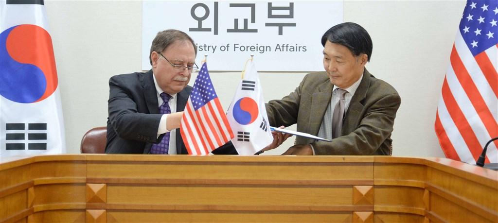 南韓外交部韓美防衛費分擔談判代表張元三(右)和美國談判代表貝茲(左)簽署第10份防衛費分擔協定。(韓聯社提供)